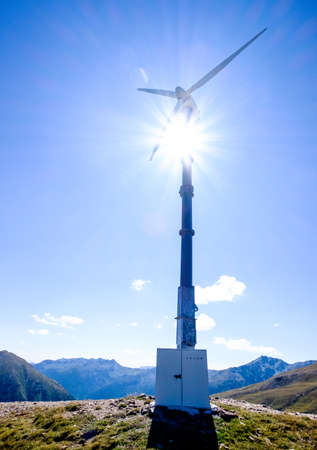 the bigger picture: modern wind generator in front of blue sky