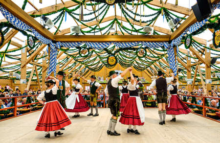 """MUNICH, GERMANY - SEPTEMBER 21: people in the """"traditon""""-beer tent at the biggest folk festival in the world - the octoberfest on september 21, 2017 in munich."""