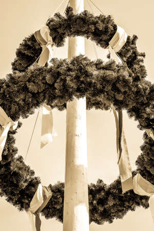 typical bavarian maypole in front of blue sky