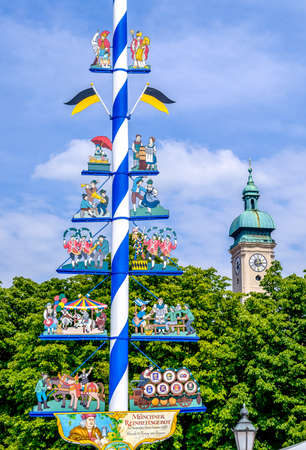 MUNICH, GERMANY - AUGUST 8: typical bavarian maypole in front of blue sky and a church tower at the viktualienmarkt in munich on August 8, 2017