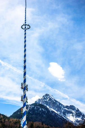 Typical bavarian maypole in front of blue sky Stock Photo