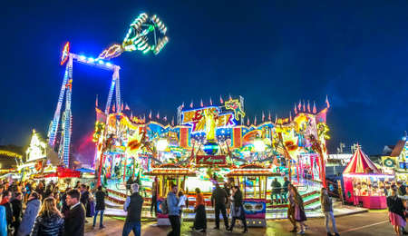 Munich, Germany - October 4: people and fairground rides at the biggest folk festival in the world - the oktoberfest on oktober 4, 2018 in munich.
