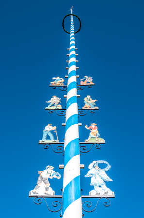 Mittenwald - Germany, November 16: typical bavarian maypole with paintings in front of blue sky in mittenwald, bavaria/germany on november 16, 2018 Editorial
