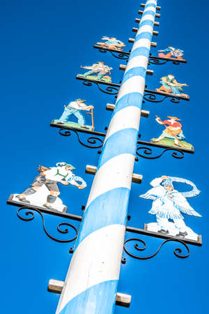 Mittenwald - Germany, November 16: typical bavarian maypole with paintings in front of blue sky in mittenwald, bavariagermany on november 16, 2018 Editorial
