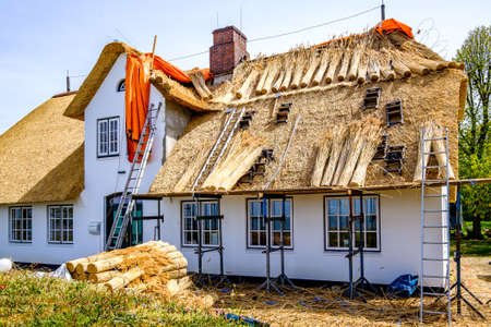 tiling a new typical thatched roof at a house in north germany