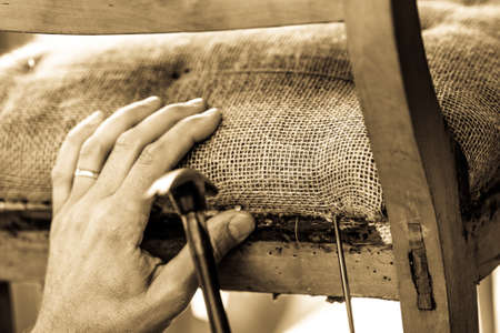 upholsterer is working at an old chair Reklamní fotografie