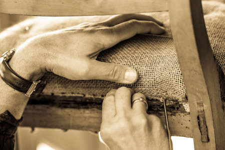 upholsterer is working at an old chair Stockfoto