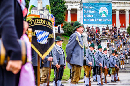 Munich, Germany - October 2019: The traditional marksmen parade with brass bands on the last day of the Oktoberfest. 60 shooters shoot a salute at the foot of the Bavaria statue on October 6, 2019 in Munich Editorial