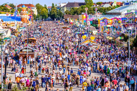 Munich, Germany - September 27: visitors, beertents and fairground rides on the oktoberfest in munich at September 27, 2019 Standard-Bild - 140142256