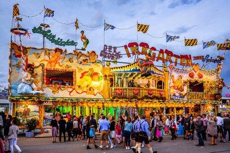 Munich, Germany - September 27: visitors, beertents and fairground rides on the oktoberfest in munich at September 27, 2019 Standard-Bild - 140142339