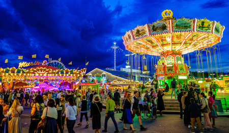 Munich, Germany - September 27: visitors, beertents and fairground rides on the oktoberfest in munich at September 27, 2019 Standard-Bild - 140142342