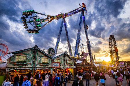 Munich, Germany - September 27: visitors, beertents and fairground rides on the oktoberfest in munich at September 27, 2019 Standard-Bild - 140142343
