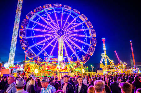 Munich, Germany - September 28: visitors, beertents and fairground rides on the oktoberfest in munich at September 28, 2019 Standard-Bild - 140142346