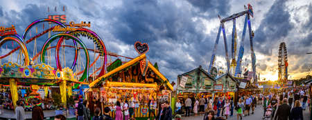 Munich, Germany - September 27: visitors, beertents and fairground rides on the oktoberfest in munich at September 27, 2019 Standard-Bild - 140142357