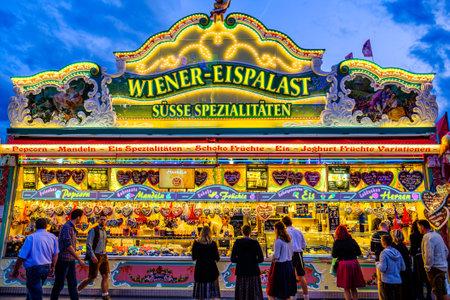 Munich, Germany - September 27: visitors, beertents and fairground rides on the oktoberfest in munich at September 27, 2019 Standard-Bild - 140142359
