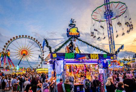 Munich, Germany - September 27: visitors, beertents and fairground rides on the oktoberfest in munich at September 27, 2019 Standard-Bild - 140142362