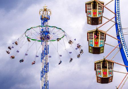 Munich, Germany - September 27: visitors, beertents and fairground rides on the oktoberfest in munich at September 27, 2019 Standard-Bild - 140142364
