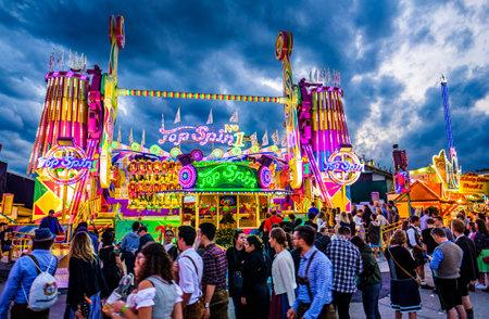 Munich, Germany - September 27: visitors, beertents and fairground rides on the oktoberfest in munich at September 27, 2019 Standard-Bild - 140142371
