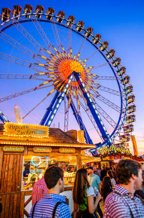 Munich, Germany - September 28: visitors, beertents and fairground rides on the oktoberfest in munich at September 28, 2019 Standard-Bild - 140142384