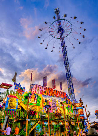 Munich, Germany - September 27: visitors, beertents and fairground rides on the oktoberfest in munich at September 27, 2019 Standard-Bild - 140142377