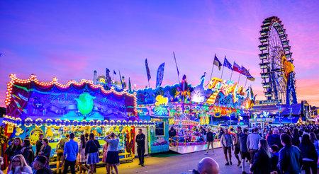 Munich, Germany - September 28: visitors, beertents and fairground rides on the oktoberfest in munich at September 28, 2019 Standard-Bild - 140142869