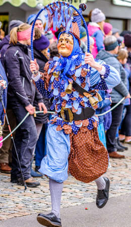 Mittenwald, Germany - February 20: participants of a parade with traditional disguise with large wooden masks and historic costumes called 'maschkera' on February 20, 2020 in Mittenwald