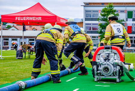 Murnau, Germany - June 24: fire fighter at an exercise with water pump in Murnau on June 24, 2017 Редакционное