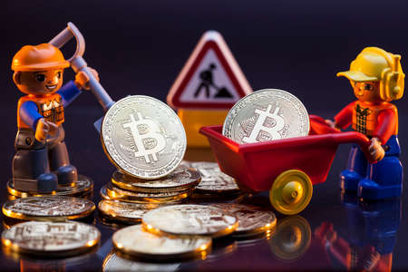Plastic toy workers with bitcoin cryptocurrency tokens, bitcoin crypto currency mining concept visualization