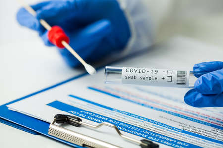 Medical worker holding Coronavirus COVID-19 NP OP swab sample test kit, nasal collection equipment, CDC submitting form, reverse transcription RT-PCR DNA molecular nucleic acid diagnostic procedure