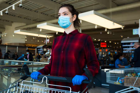 Business as usual,open again as normal,new norm for everyday activities after COVID-19 Coronavirus pandemic end,obligatory personal protective equipment,face mask,gloves.Female shopper pushing trolley