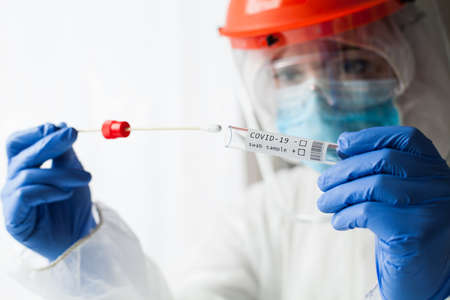 Physician wearing personal protective equipment performing a Coronavirus COVID-19 PCR test, patient nasal NP and oral OP swab sample specimen collection process, viral rt-PCR DNA diagnostic procedure