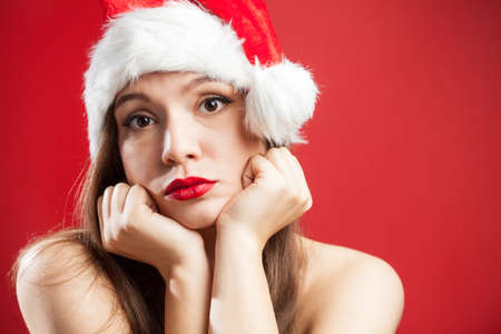 Worried depressed attractive caucasian brunette woman dressed as Mrs Santa Claus,wearing red white hat,chin on hands,isolated on red background,copy space,New Year 2021 COVID-19 Coronavirus pandemic Imagens
