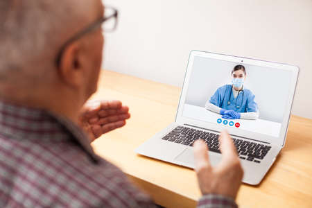 Young NHS GP physician and elderly male patient consulting over video call,virtual medical health check-up,doctor tele visit instead of in-office appointment during COVID-19 pandemic outbreak lockdown