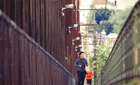 An Unidentified Man Walking the Train Bridge