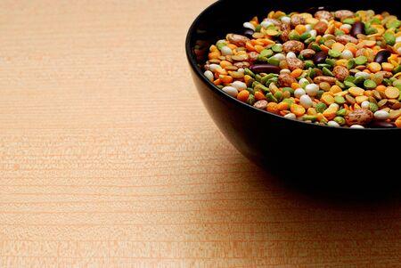 leguminosas: Tazón de fuente negro con diversos tipos de legumbres, Fondo naranja Foto de archivo