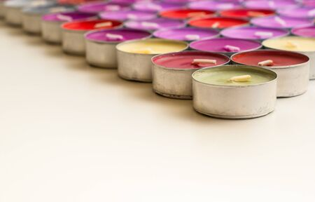 tea candles: Colored Tea Candles in Triangle Shape on White Desk Front View