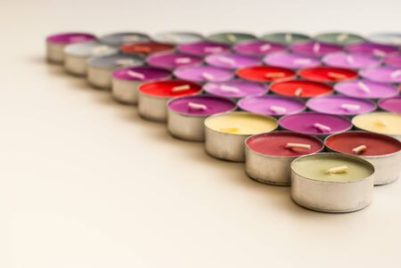 tea candles: Colored Tea Candles Arrangeds Triangle Shape on White Desk Stock Photo