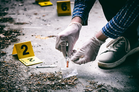 Crime scene investigation, tossed syringe on the ground Stock Photo