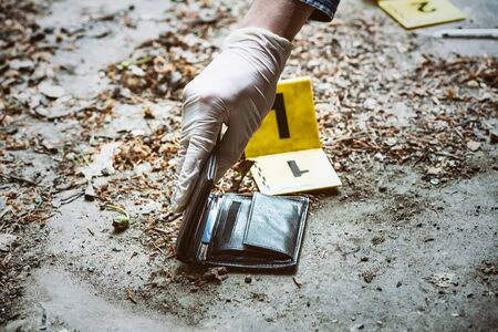 Crime investigation, yellow crime scene marker next to the wallet on the ground Stock Photo