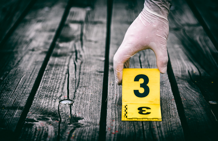 Crime scene investigation, putting the crime scene marker on wood ground Stock Photo