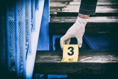 Crime scene investigation, putting the crime scene marker on wood stairs Stock Photo