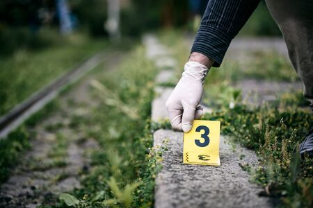 Placing the crime scene marker on the ground near train track Stock Photo