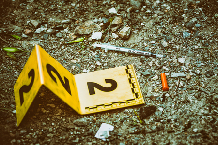 Crime scene marker next to tossed syringe on the ground Stock Photo