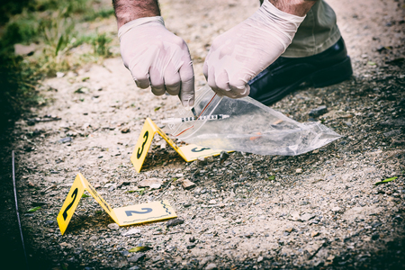 Crime scene investigation, picking up the tossed syringe and putting it to the plastic bag Фото со стока