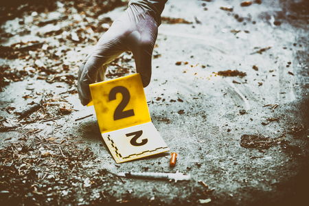 Putting the crime scene marker on the ground next to syringe