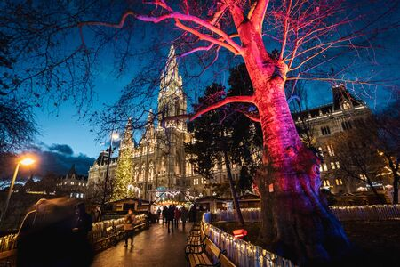Vienna, Austria - December 10 2018: Night shot of Christmas markets at Rathausplatz, lighted ornate tree, town hall in the background Redakční