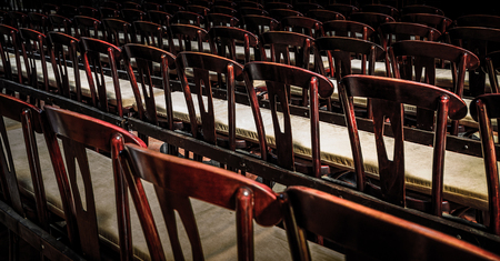 Wooden chairs in a row in a church,