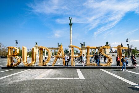 Budapest, Hungaria - April 9 2019: Text Budapest made from wood on Heroes Square, Millennium Monument in the background