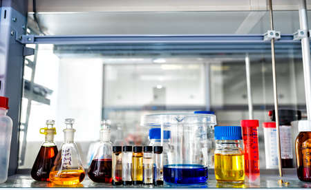 Closeup of laboratory glassware filled with various colored liquids, science and research background, selective focus Stock Photo