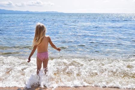 Little girl on the sunny coast Stock Photo